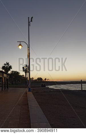 View Of The Sea And Lamppost On The Pedregalejo Beach At Dusk.