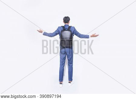 Back view full length young handsome businessman  wearing blue suit with white shirt ,tie and blue pants with white sneaker with black backpack showing both hands open palms,