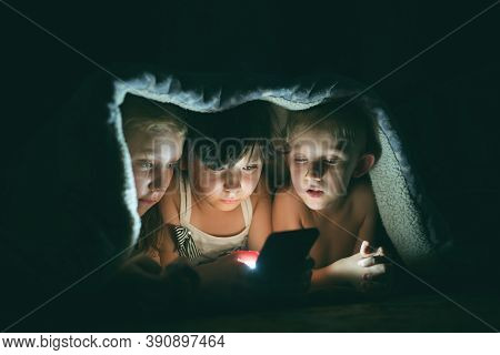 Children Play Games On A Smartphone At Night Under A Blanket On The Floor, The Child Rewrites With F