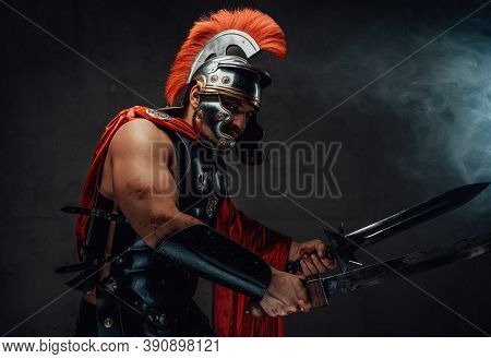 Armoured Savage And Brutal Roman Warrior In Red Cloak With Helmet Attacks Holding Swords In Smokey B