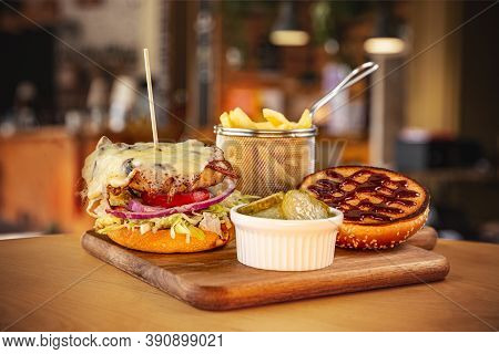Brioche Bun With Burger, Pickled Cucumber And French Fries