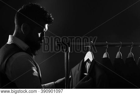 Man In Suit. Shirts And Suits In A Male Luxury Store. Row Of Man Suit Jackets On Hangers. Tailor In