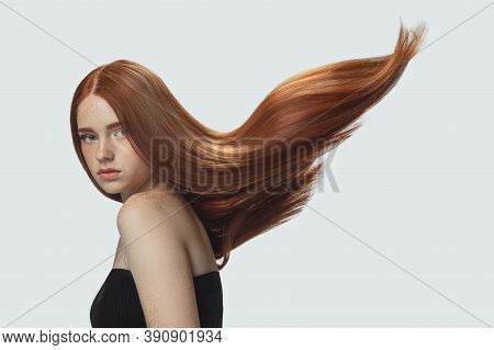 Beautiful Model With Long Smooth, Flying Red Hair Isolated On White Studio Background. Young Caucasi