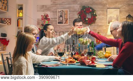 Little Daughter At The Table With The Family Celebrating Christmas. Family Eating Tasty Food. Tradit