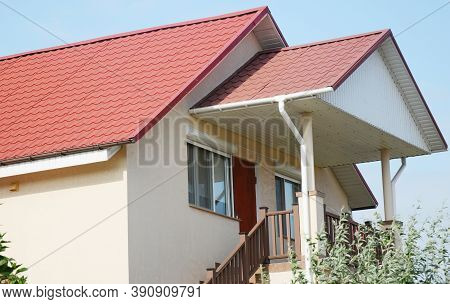 A Close-up On A Stucco House With A Red Metal Tiled Gabled Roof With Soffit And Fascia Boards, Rain