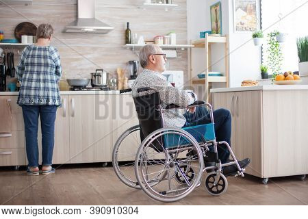 Disabled Man Sitting In Wheelchair In Kitchen Looking Through Window While Wife Is Preparing Breakfa