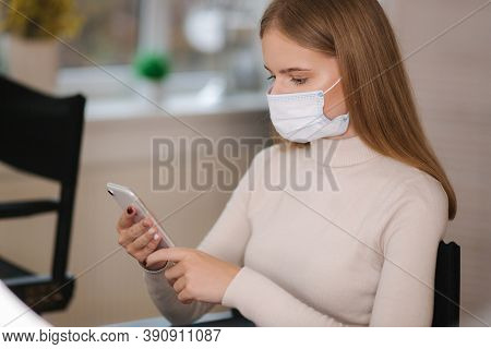 Female Customer In Beauty Salon Sitting In Medical Mask And Use Phone. Beautiful Young Blond Hair Wo