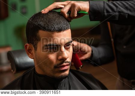 African-american Barber's Hand Uses Razor And Haircut On Hispanic Latino Man With Goatee In A Barber