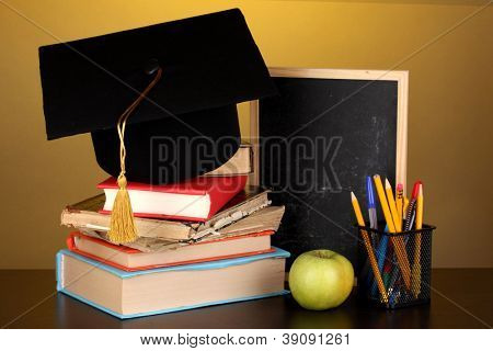 Books and magister cap against school board on wooden table on yellow background