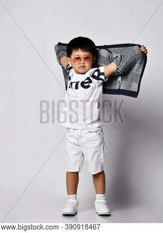 Asian Korean 6-7 Y.o. Kid Boy In Sunglasses White T-shirt And Shorts Stands Holding His Hands Up Wit