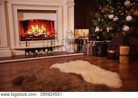 Winter Holidays Atmosphere In A Warm Room With A Christmas Tree Full Of Lights And Toys Near A Cute