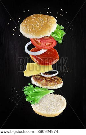 Levitating Sandwich Cheeseburger Ingredients On Dark Background. Burger Components Floating In The A