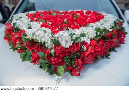 Luxury Wedding Car Decorated With Flowers . White, Red Heart Bouquet On White Bridal Car. Wedding Ca