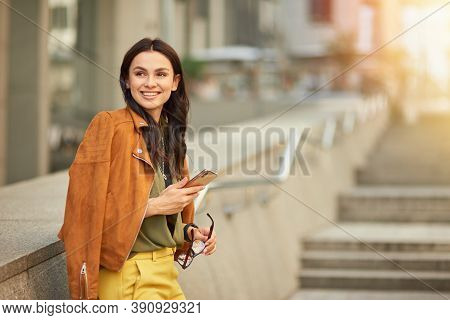 Side View Of A Young And Happy Cheerful Business Woman Using Her Smartphone And Smiling, Looking Asi