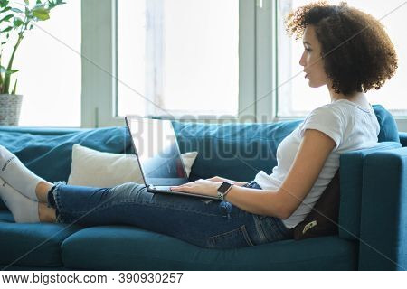 African American Woman Uses Laptop At Home. Beautiful Young Lady Is Sitting On The Couch And Working