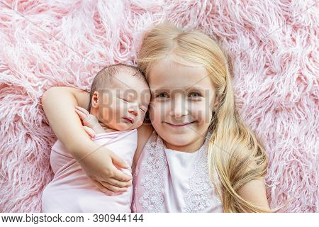 Little Girl And Her Newborn Sister. Toddler Kid Meeting New Sibling. Cute Girl And New Born Baby Rel