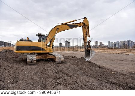 Excavator Working At Construction Site On Groundwork. Backhoe Digs Gravel And Concrete Crushing. Rec