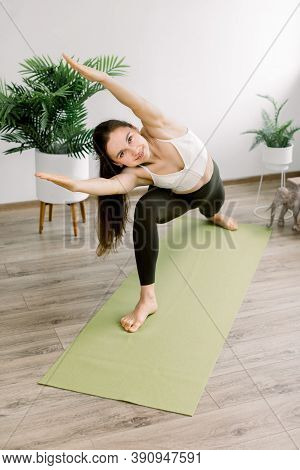 Beautiful Sporty Fit Young Woman Practices Yoga Asana On Green Yoga Mat At Cozy Light Fit Hall. Yoga