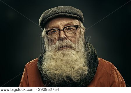 Portrait of a serious old man with long white beard wearing a cap and a scarf and looking at camera. Old age concept. Black background.