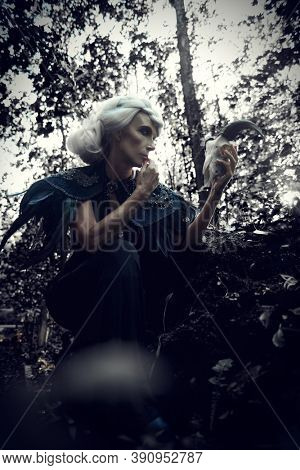 An aristocratic old widow woman with beautiful gray hair and a rich black dress is posing sad in a crypt in a cemetery. Black Widow. Atmosphere of mysticism. Halloween.