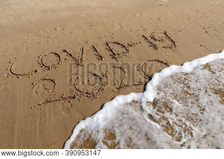 View Of Covid-19 And 2020 Text In Sand On Beach Is Covered By Ocean Wave And Disappears