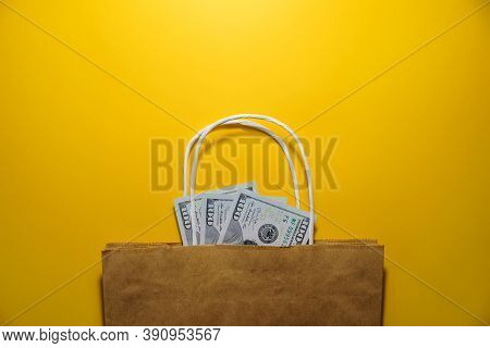 Money, Bag On A Yellow Background, Top View. Dollars In A Shopping Bag. Shopping, Black Friday, Sale