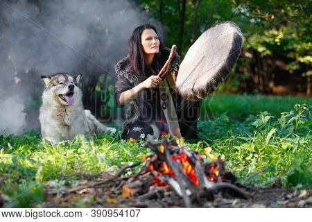 Shaman Woman Playing Her Shaman Sacred Drum In The Evening Forest By The Fire, The Big Dog Alaskan M