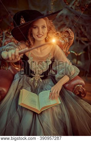 Portrait of a charming woman witch in a hat and beautiful dress sitting in an armchair with a book of spell and with a magic wand in the old castle. Halloween. Celebration.