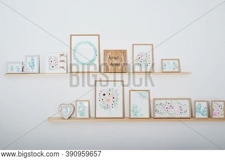 Watercolor Flowers Pictures On Wall. Shelves With Picture Frames On White Background. Creative Works
