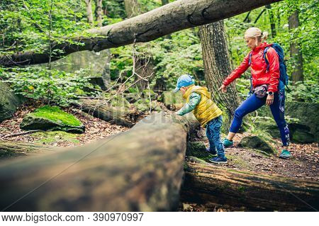 Little Boy Hiking With Mother, Family Adventure. Small Child Walking In Rocky Green Forest.