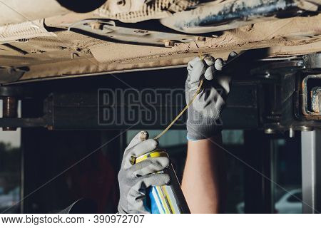 Car Mechanic Purges Carburetor Channels With Auto Body Bottom.