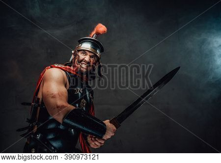 Armoured Savage And Brutal Roman Warrior In Red Cloak With Helmet Attacks Holding Sword In Smokey Ba