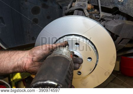 New Brake Disc With An Anti-corrosion Layer, Mounted On The Front Hub, Screwing The Disc With A Pneu