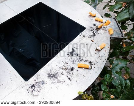 Detail of unlit cigarette butts on public trash. Concept