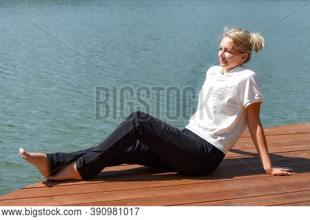 Young Woman Resting On Shore, Relaxing Outdoor Recreation. A Moment Of Calm In The Fresh Air.