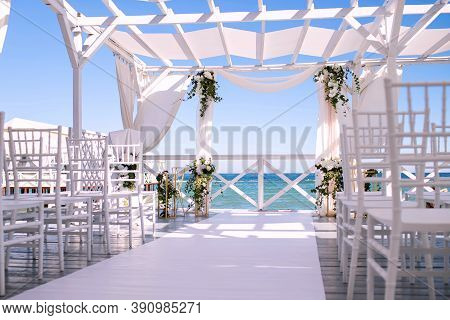 Wedding Arch Against The Background Of The Sea, Fresh Flowers On A White Wood Decor, Beautiful Sunny