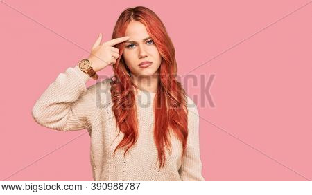 Young redhead woman wearing casual winter sweater pointing unhappy to pimple on forehead, ugly infection of blackhead. acne and skin problem