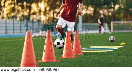 Boys Running Soccer Balls Between Training Cones. European Football Sports Summer Camp For Youth Ath