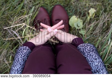 Top View Of Person Sitting On The Grass With His Hands Clasped Around His Knees