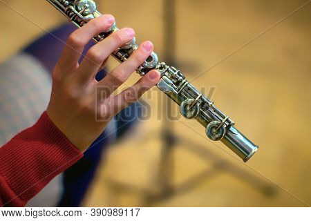 The Girl Is Holding A Large Concert Flute (in Hands Close-up). Professional Musician At The Rehearsa