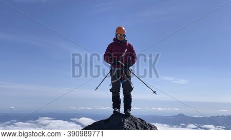 A Climber With Trekking Poles Stands On The Top Of The Mountain. Trekking In The Klyuchevskoy Volcan