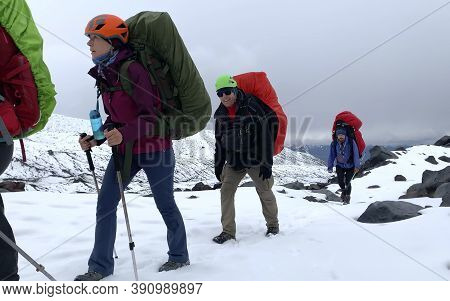 Group Of Mountaineers With Large Backpacks And Trekking Poles Is Walking Along A Snow-covered Trail.