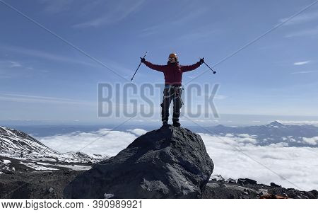 Climber With Trekking Poles On The Top Of The Mountain. Mountain Climbing. Trekking In The Klyuchevs
