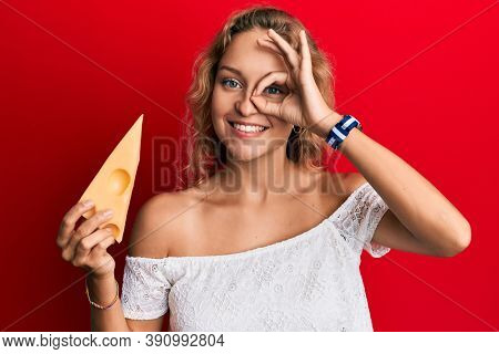 Beautiful caucasian woman holding a piece of emmental cheese smiling happy doing ok sign with hand on eye looking through fingers