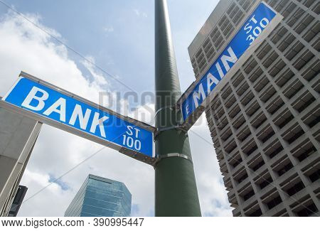 Close View Of Bank And Main Street Signs On A Lamppost In Norfolk Downtown (west Virginia).