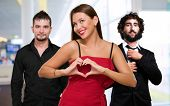 Woman Standing In Front Of Men Making A Heart Shape Sign, Indoor poster