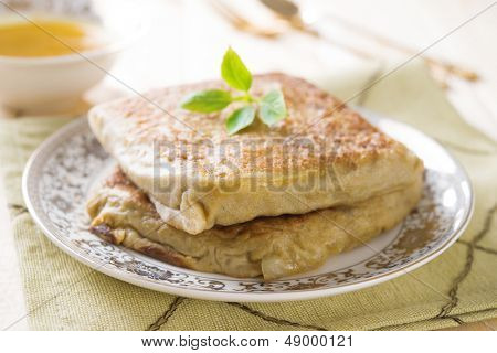 "Mutabbaq or Murtabak is a stuffed Arabic bread, also known as ""Fatatari"" ; in some parts of Middle East. poster"