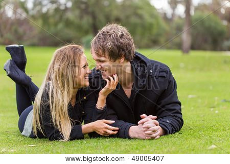 Happy young attractive couple portrait, looking each other on the grass