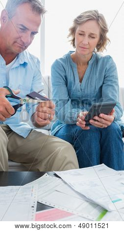 Wife watching her husband cut credit card in half at home in the living room