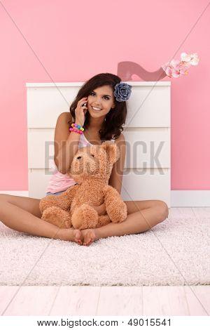 Junges Mädchen im Chat auf mobile, lächelnd, auf Boden in ihrem Rosa Zimmer mit Teddybär sitzend.